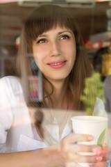 Smiling young woman at the cafe with cup of coffee or tea