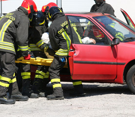 firefighters in action and pull the injured from the car