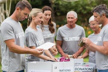 Happy volunteer looking at donation box