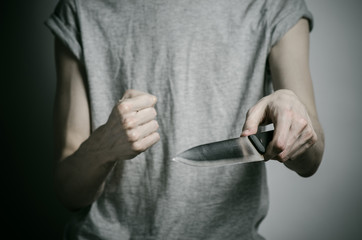 a man holding a knife on a gray background studio