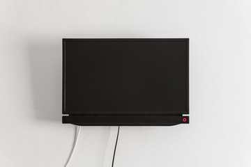 Black LCD or LED tv screen hanging on a wall
