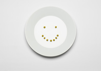 green peas lying on a white plate cheerful smile top view