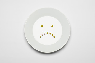 green peas lying on a white plate a sad smile top view