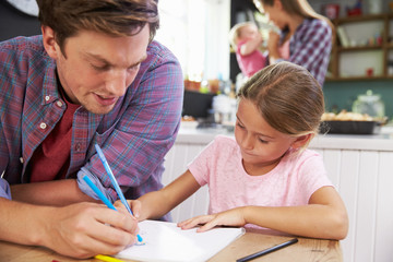 Father Helping Daughter To Draw Picture At Kitchen Table