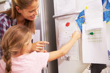 Mother And Daughter Putting Star On Reward Chart