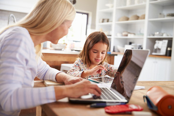 Mother using laptop computer with her young daughter