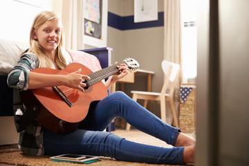 Girl playing guitar in her bedroom