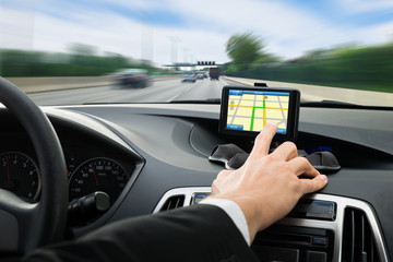 Person's Hand Using Gps Navigation System In Car