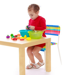 The girl sitting at the table and plays artificial fruit