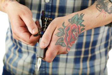 Hand of tattoo artist with tattoo machine, closeup
