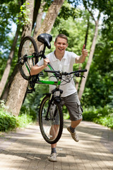 Happy young man holding a  bicycle
