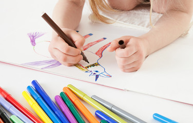 Unrecognizable little girl drawing a narwhal - closeup shot