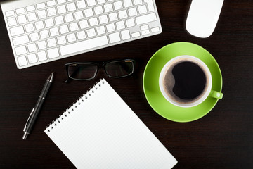 Office desk table with computer, supplies, coffee and glasses