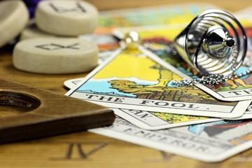 Tarotkarte THE FOOL mit Pendel und Runensteinen auf Ouija