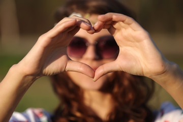 Beautiful woman hippie doing hands heart and shows it