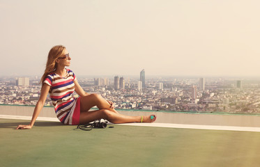 Beautiful hipster woman on the roof of skyscraper