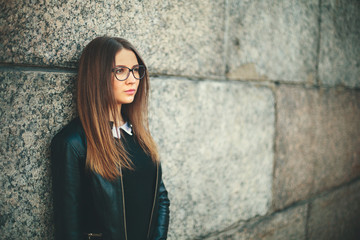 Portrait of a young hipster student girl with glasses thinking near the wall of college