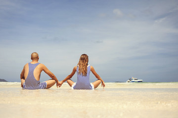 Attractive love couple on the beach in swimsuits on vacation