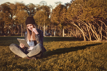 Young student hipster girl with tablet sitting in park, reading and listening to music