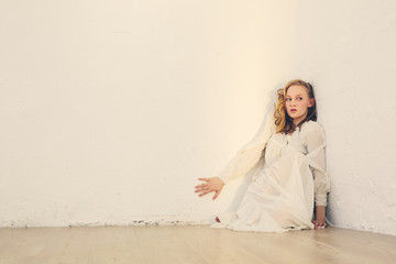 scared young beautiful woman with long curly hair sitting near white wall in the room