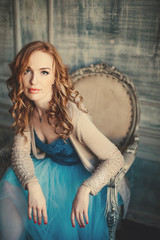 Beautiful glamor woman with red hair in a luxury interior sitting on retro chair