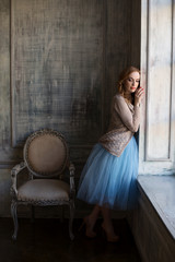 Elegant woman is standing near the window in luxury interior room