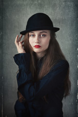 young beautiful girl in a hat (old style with a paper texture)