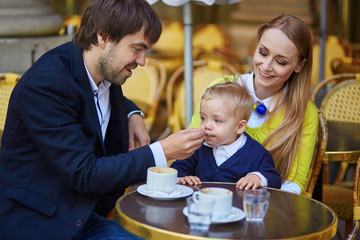 Happy family of three in cafe