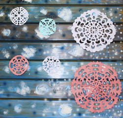 Picturesque paper snowflakes on a blue wooden table, a Christmas