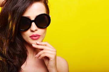 junge frau mit sonnenbrille vor gelben hintergrund