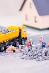Road works with miniature workers close-up
