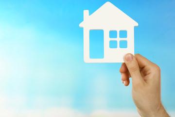 Female hand holding house on turquoise background