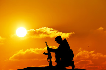 Silhouette shot of soldier holding gun with colorful sky and mou