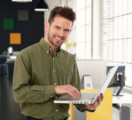Happy casual businessman with laptop computer