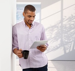 Casual afro american office worker reading tablet