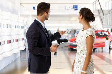 Salesman and client at the car dealership indoors