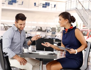 Happy businesswoman with male client at car saloon