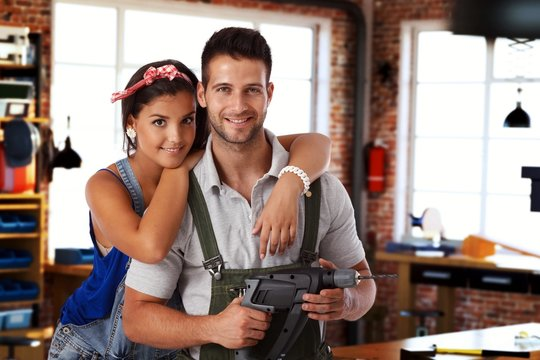 Happy young couple standing at home workshop