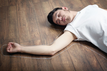 Crime scene simulation, young man lying on floor