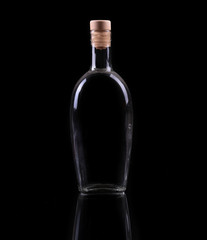 Bottle and glass with alcohol isolated on black.