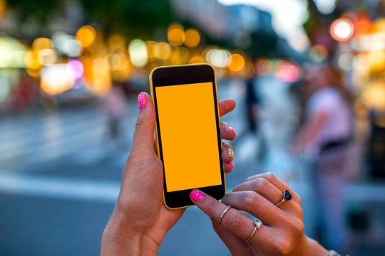 Holding phone on street background