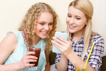 Pair of women looking at phone in cafe