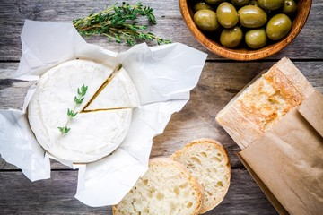 Whole Camembert cheese with thyme, olives and baguette