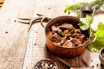 Venison Goulash in Copper Pot on Wooden Surface
