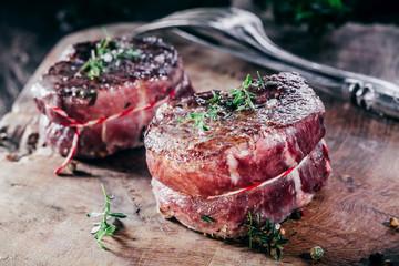Rare Seasoned Beef Steak Filets on Wooden Board