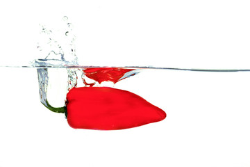 Pepper falling into water with a splash