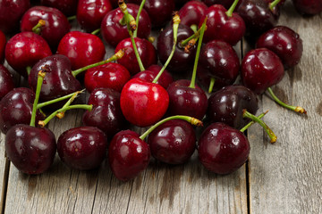 Ripe whole black cherries on rustic wood ready to eat