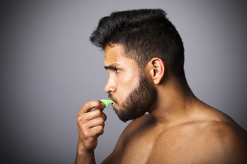 Joven latino con barba soplando pito