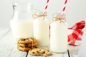 Two bottles of milk with cookies on white  background