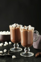 Glasses of hot chocolate with marshmallows on black background